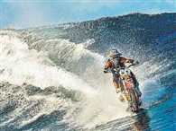 Stunt rider Robbie Maddison surfs waves on a dirt bike