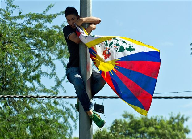 Tibetan activists waves a Tibetan flag