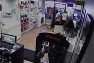 Crowd laughs at robbers after they get locked inside phone shop