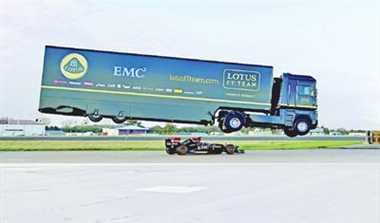 F1 transporter truck breaks world record by   jumping over speeding Lotus race car