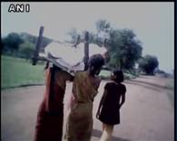 Women dismantle roof of their house for some wood for mother's funeral