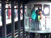Three teenagers hanging behind subway train