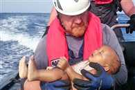 drowned migrant baby in mediterranean sea in arms of a German rescuer