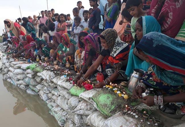 बाढ़ से उफनाई नदियां, मनाने के लिए शुरू हुई नदियों की पूजा, देखें तस्वीरें...